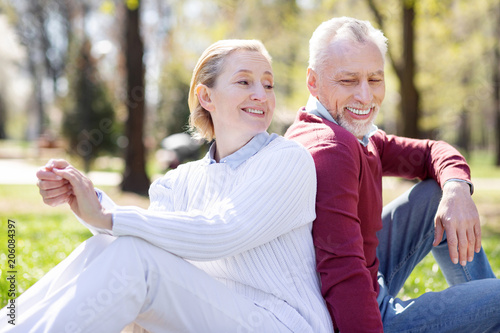 On a picnic. Nice cheerful couple sitting together on the grass while resting in the park