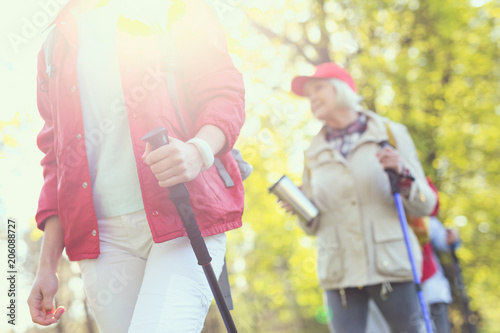 Great weather. Young sportive woman holding a stick and an old woman following her