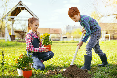 Flower planting. Nice strong boy holding a spade while planting flowers together with his sister