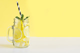 Fresh summer fruits water or lemonade with lemon and mint on yellow background. Close up.