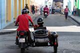 Santiago de Cuba, CUBA Couple riding in motorcycle with sidecar on the road ni Santiago de Cuba.