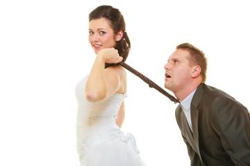Dominant bride wearing wedding dress pulling groom tie