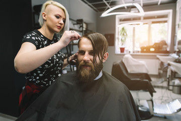 Stylish hairdresser cutting hair of client at barber shop. Beard man getting haircut at salon.