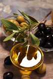 Bottle virgin olive oil and oil in a bowl with some olives - 206116542