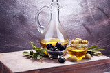 Bottle virgin olive oil and oil in a bowl with some olives - 206116562