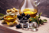 Bottle virgin olive oil and oil in a bowl with some olives - 206116596