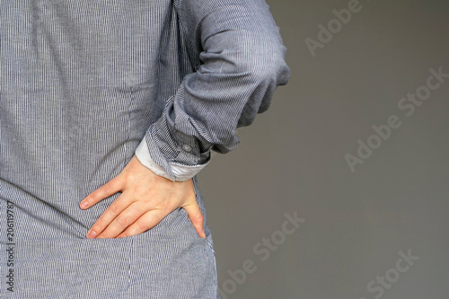 Close-up view of a young woman with pain in kidneys isolated on a gray background. Young woman with back ache clasping her hand to her lower back. Woman suffering from ribbing pain, waist pain.