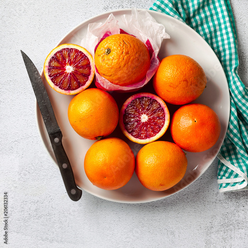 A group of oranges on a plate. some of them cut. knife and towel