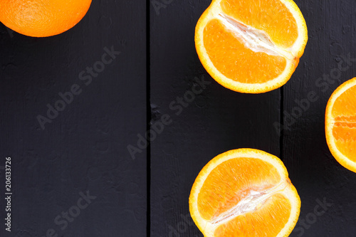 Fruits of oranges on a black wooden background, halves of oranges on wooden boards. Citrus for Vegetarian Breakfast