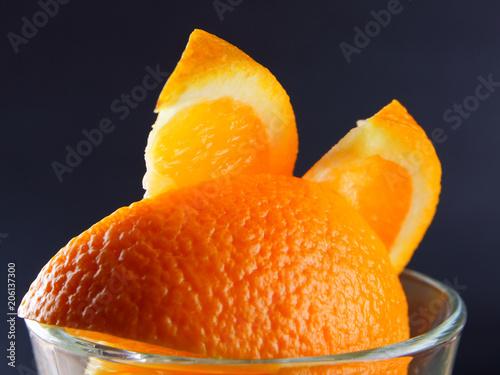 Kawałki tropikalnych owoców w szklance. Koktajl owocowy na czarnym tle. Plastry pomarańczy, kostki kiwi, plastry ananasa w szklanej misce. Owoce cytrusowe