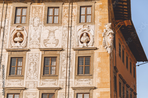 close up of ancient house with sculptures in old european city, Pisa, Italy