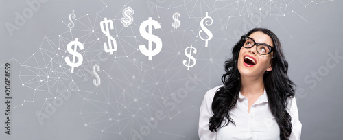 Dollars with happy young businesswoman on a gray background