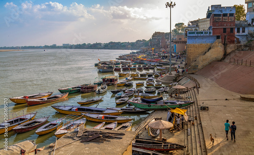 Aerial view of Varanasi city architecture with wooden boats at the Ganges river bank at sunset. Varanasi is a historic religious Indian city.