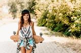 Portrait of beautiful brunette girl hold her wooden longboard skateboard