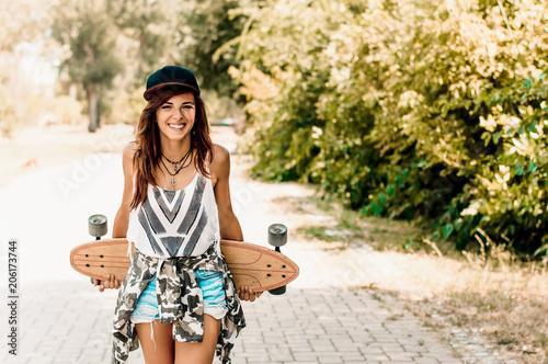 Plexiglas Skateboard Portrait of beautiful brunette girl hold her wooden longboard skateboard