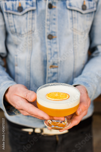 Man in a blue jean jacket holding a bright orange alcoholic drink in a cocktail glass, garnished with dried orange.