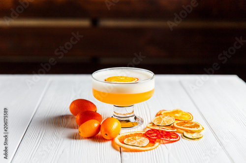 A photo of a bright orange alcoholic drink in a cocktail glass, garnished with dried orange, lime and grapefruit and fresh cumquat. White wooden table.