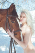 Young blonde woman hug her horse, winter time