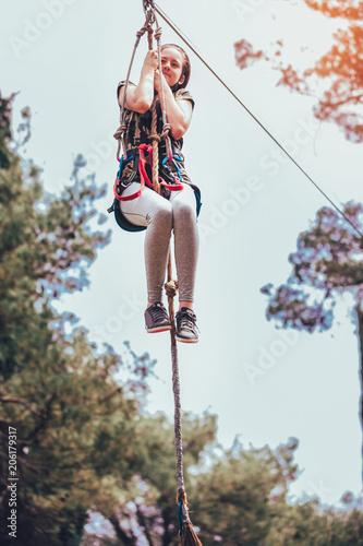 Fotobehang Amusementspark Happy school girl enjoying activity in a climbing adventure park on a summer day