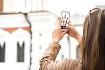 Young woman in Tallinn, Estonia, taking photo of Alexander Nevsky Cathedral in the old town with smartphone. Travel photography with mobile phone.