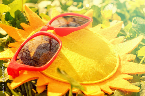 Foto Murales Yellow sunglasses on sun toy on green grass, summer is coming concept