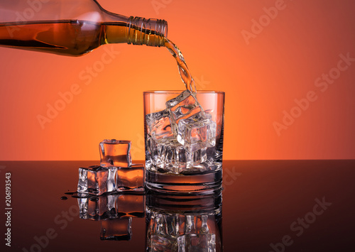 Whisky alcohol pouring into glass with ice drink on warm dark orange background