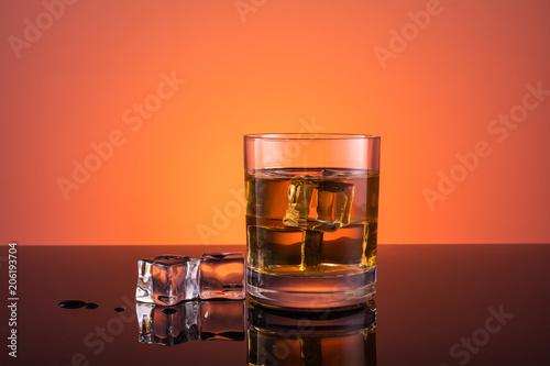Whisky alkohol w szkle z lodem, pić na ciepłym ciemnym pomarańczowym tle