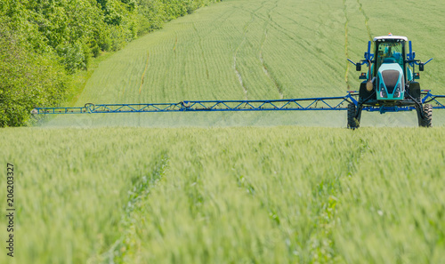 Fotobehang Trekker Agricultural sprayers, spray chemicals on young wheat.
