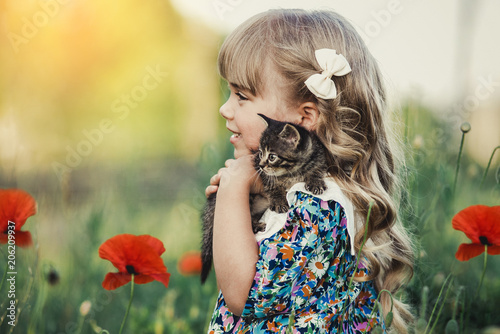 Foto Murales little girl with blond hair standing up holding a striped kitten. The kitten sits on the child's shoulder