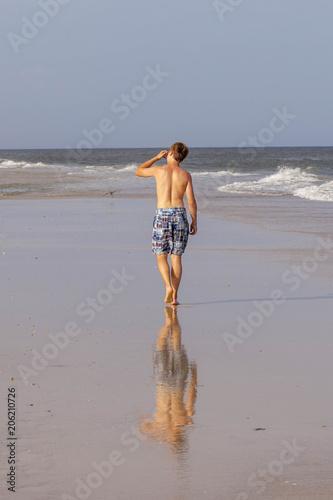ładny chłopiec jogging wzdłuż plaży