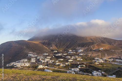 Fotobehang Canarische Eilanden village of femes in Lanzarote in morning fog and volcano