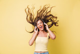 Image of cheerful woman 20s singing and enjoying tune with shaking hair while listening to music via headphones, isolated over yellow background - 206219551