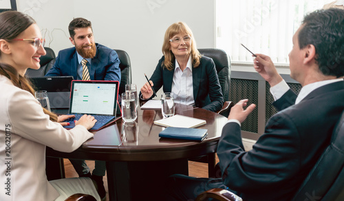 Confident business people smiling while listening to their colleague presenting a successful plan during board of directors meeting in the conference room