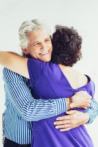 Cheerful senior man hugging wife