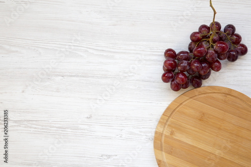Foto Murales Bunch of ripe red grape and round bamboo board on white wooden background, top view. Copy space.