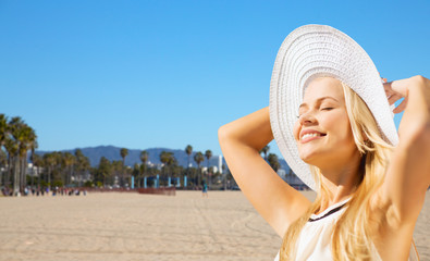 travel, tourism and summer vacation concept - beautiful woman in hat enjoying sun over venice beach background in california
