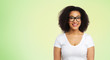 vision, body positive and people concept - happy african american woman in white t-shirt and glasses over lime green background