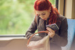 beautiful young woman in the tram, subway, train with cell phone, looking in her hand bag, purse, autumn mood colors