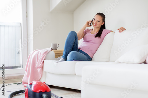 cleaning, household and technology concept - happy woman or housewife calling by smartphone with vacuum cleaner and mop in bucket on floor at home