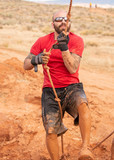 A man in sunglasses and a red shirt climbing up out of a mud pit during a mud run obstacle course - 206251106