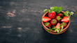 Strawberries in a plate. On a wooden background. Top view. Copy space.