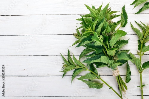 Fresh nettles On a white wooden background. Top view. Copy space.