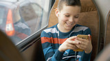 close-up shot of a young boy traveling by bus through city. He using social network on his smartphone and listens to music. - 206261523