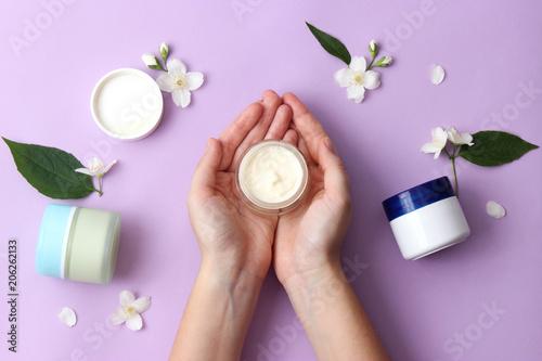 kremowe i kobiece dłonie na pastelowym tle. kompozycja kwiatów, krem do pielęgnacji i dłonie. minimalizm. krem przeciw starzeniu. Ochrona skóry. kategorycznie