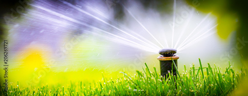 Aluminium Purper automatic sprinkler system watering the lawn on a background of
