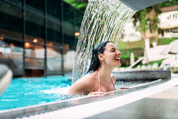 Smiling young woman enjoying under waterfall shower.