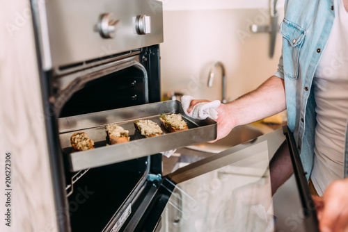 Close-up image of unrecognizable male person taking hot sandwiches from the oven.
