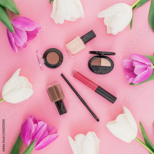 Leinwanddruck Bild Beauty composition with tulips flowers and cosmetics - lipstick, nail polish on pink background. Top view. Flat lay. Home feminine desk.