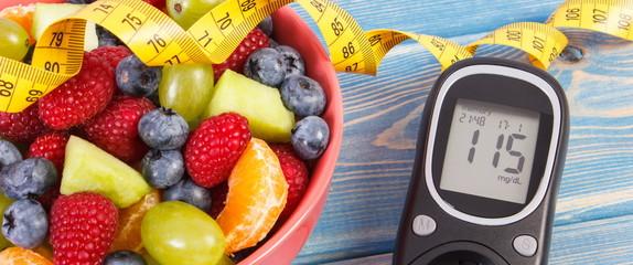 Fruit salad, glucose meter for measuring sugar level and centimeter, healthy lifestyle and nutrition concept © ratmaner