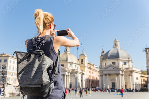 Female tourist with a fashinable vintage hipster backpack taking photo of Piazza del Popolo, People's Square, in Rome, Italy by her mobile phone.